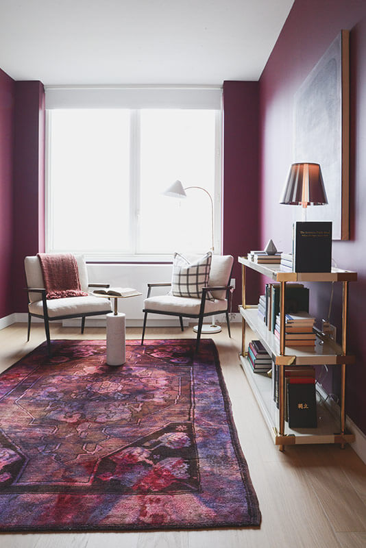 Next to the area rug stands an industrial shelf table and pair of white cushioned club chairs. The hardwood flooring contrasts with the neatly artificial room coloring.