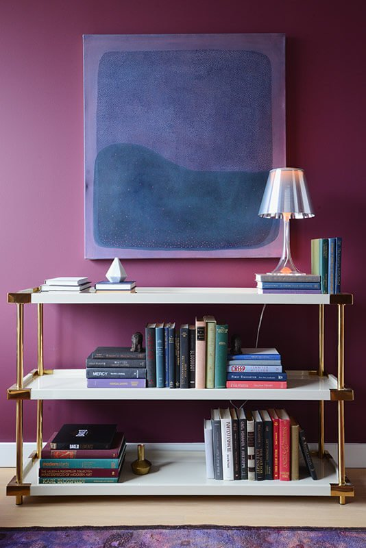 The luxurious industrial bookshelf here sports a high contrast look with white shelving and gold hardware. Above, a painting reflects the rich dark tone of the room.