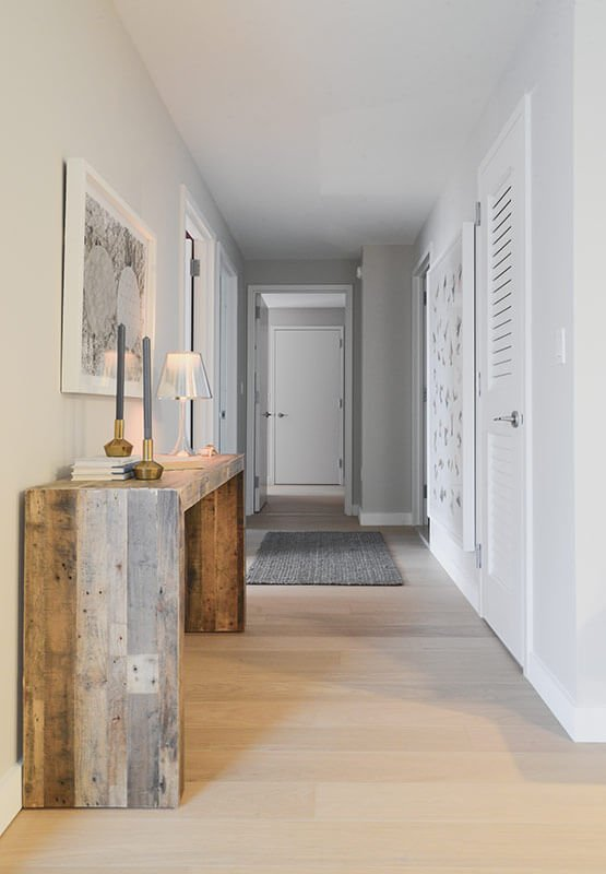 Further down the hall, we see another elegant use of rustic wood, with a minimalist end table standing at left.