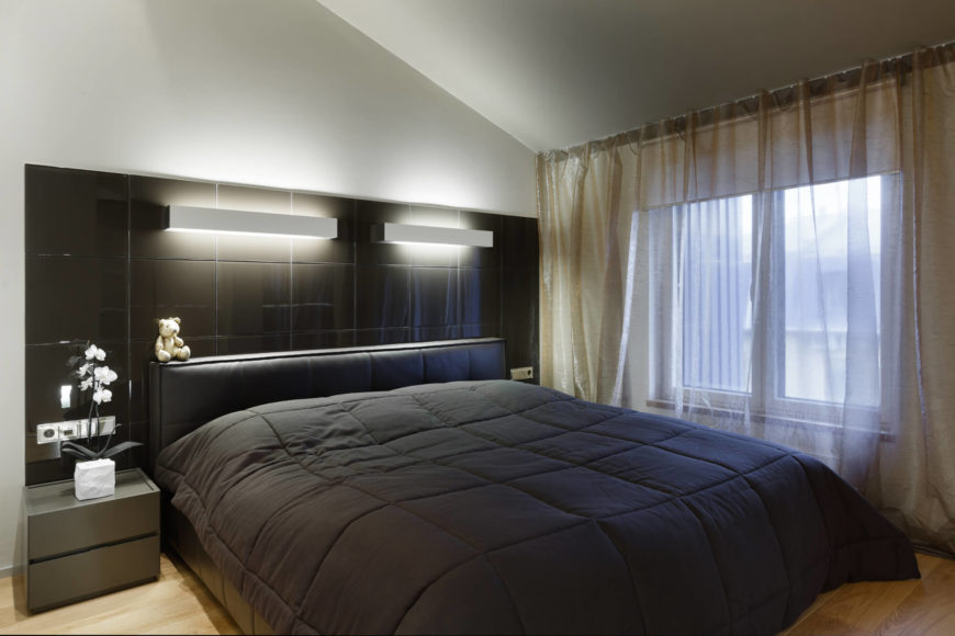 The primary bedroom is sleek and attractive. A king-sized bed is the center of attention with a colossal headboard that provides storage space and soft light. Natural hardwood floor contrasts with the the dark color of the sheets and headboard.