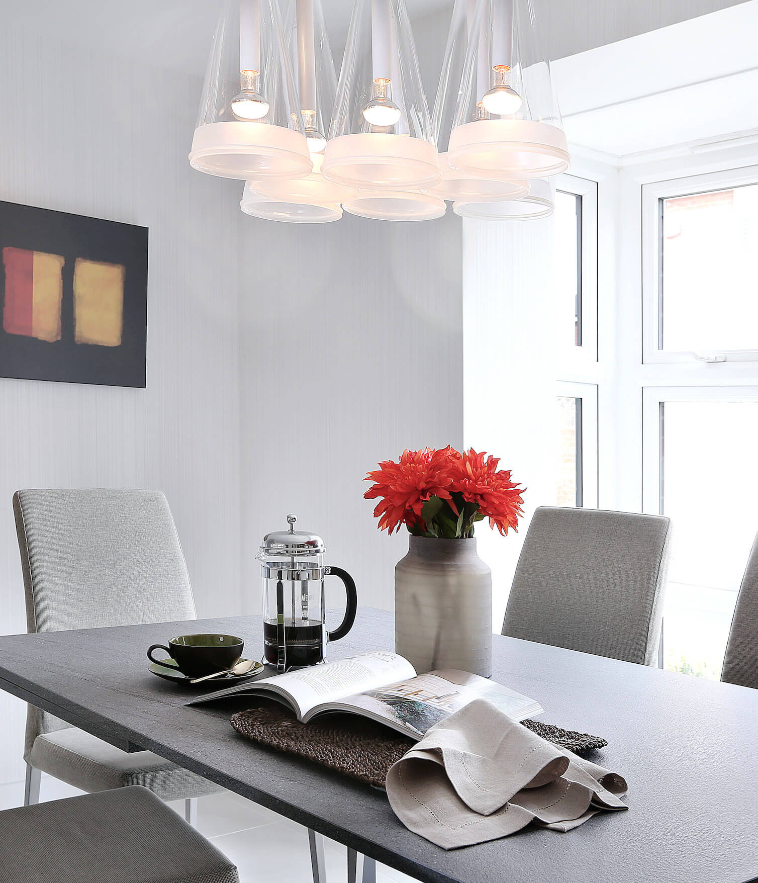 The dining room space, contained within the main open-plan area of the home, stands in neutral greys and whites, with a granite topped minimalist table at center. Flanked by lighter grey Parson chairs, the table stands beneath a set of conical pendant lights in glass.