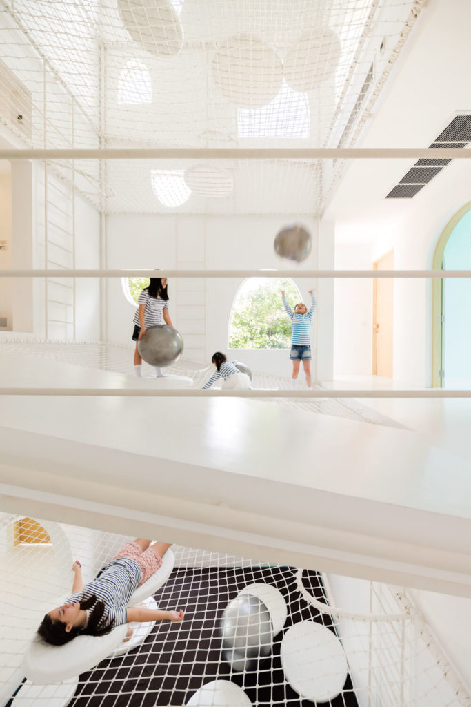 "This split-level view shows how the normal rules of home architecture simply do not apply within the playful vertical center of this home. A sloped hall wraps one of the angled net ""floors,"" as we see children occupying levels above and below."