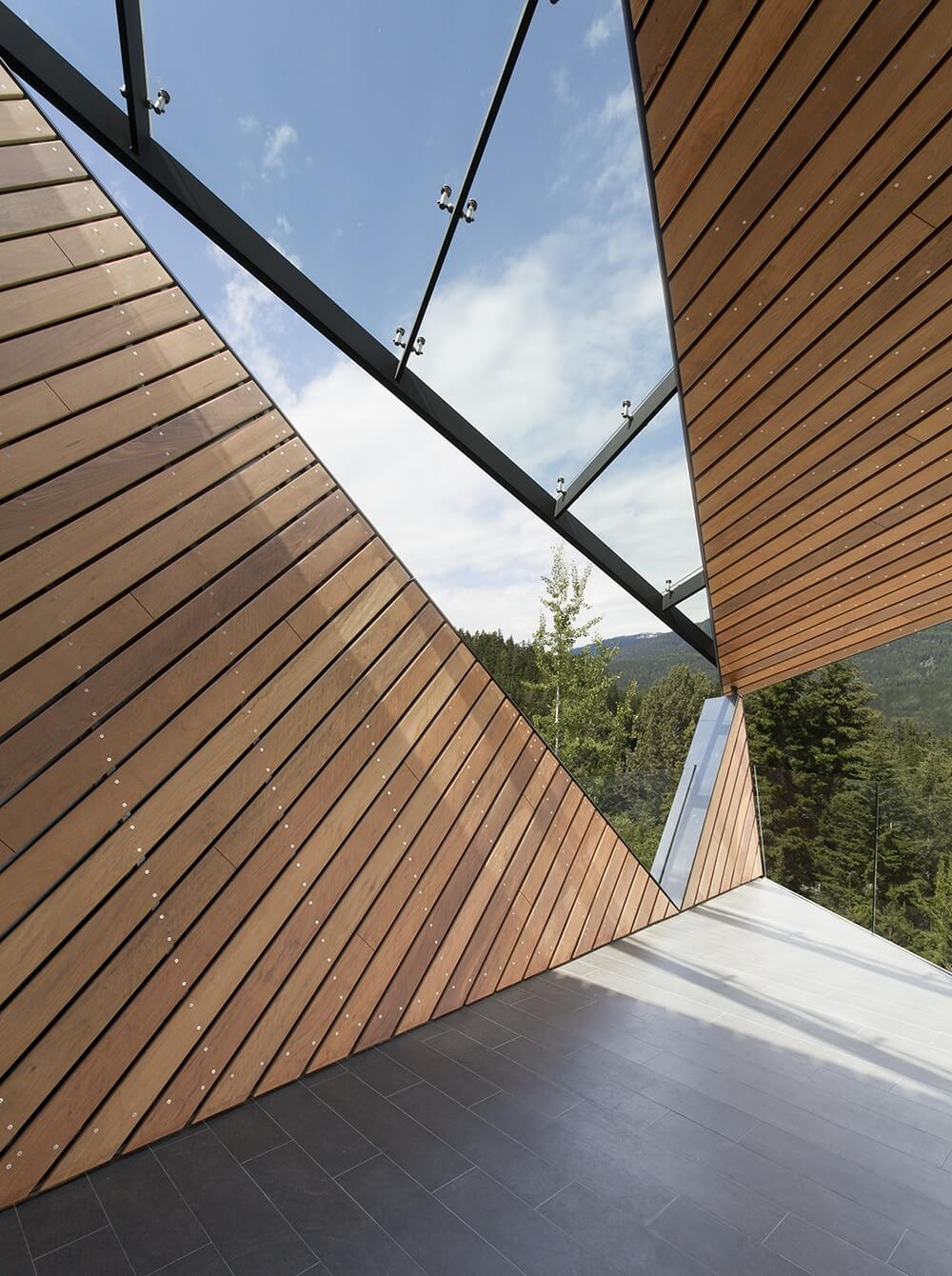 On the other side of the deck we can see the way the glass panels meet the sides and roof of the home in a dazzling angular fashion.