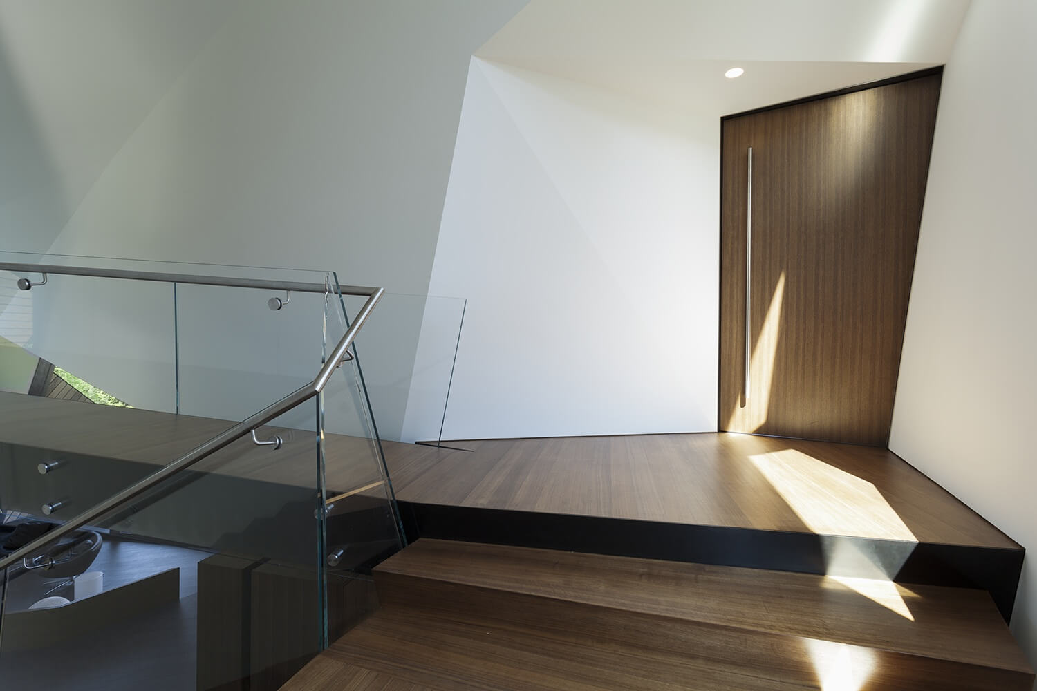 Even the doors in this home are full of angles, as displayed by this warped door. The handle is an immensely long chrome fixture for a modern and minimalist vibe.