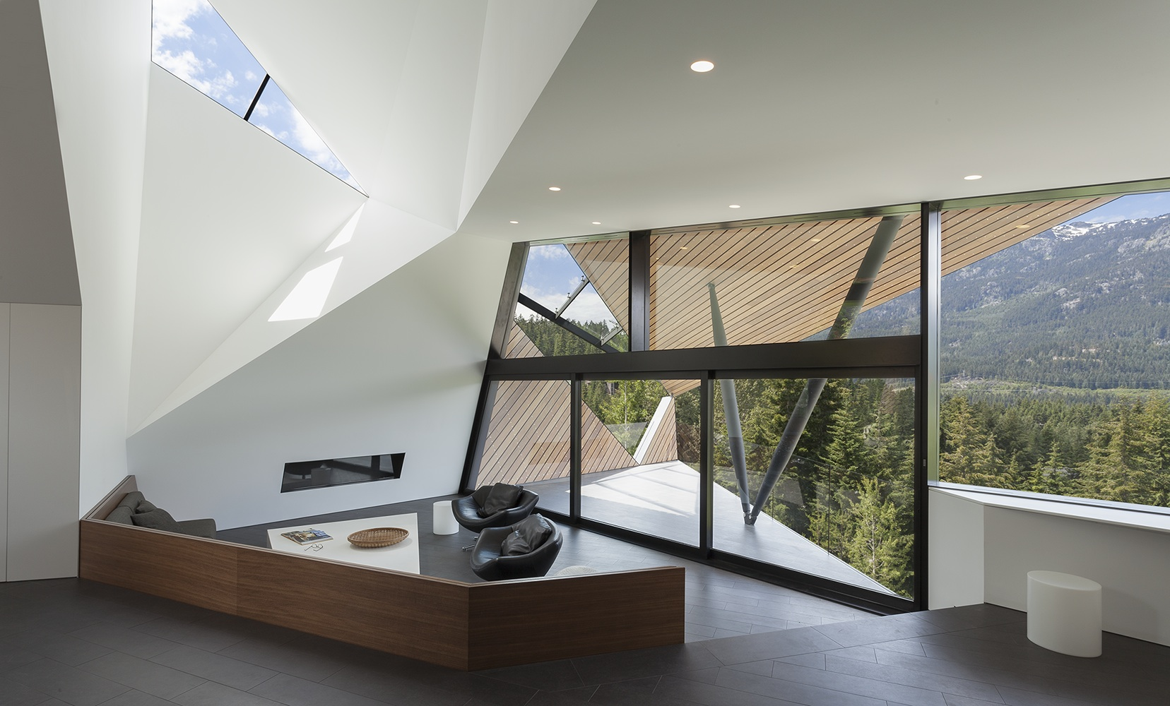 Back inside the home, we can see the small enclosed fireplace in the living room, the cozy leather chairs, and the angular skylights filtering sunshine down into the spacious area.