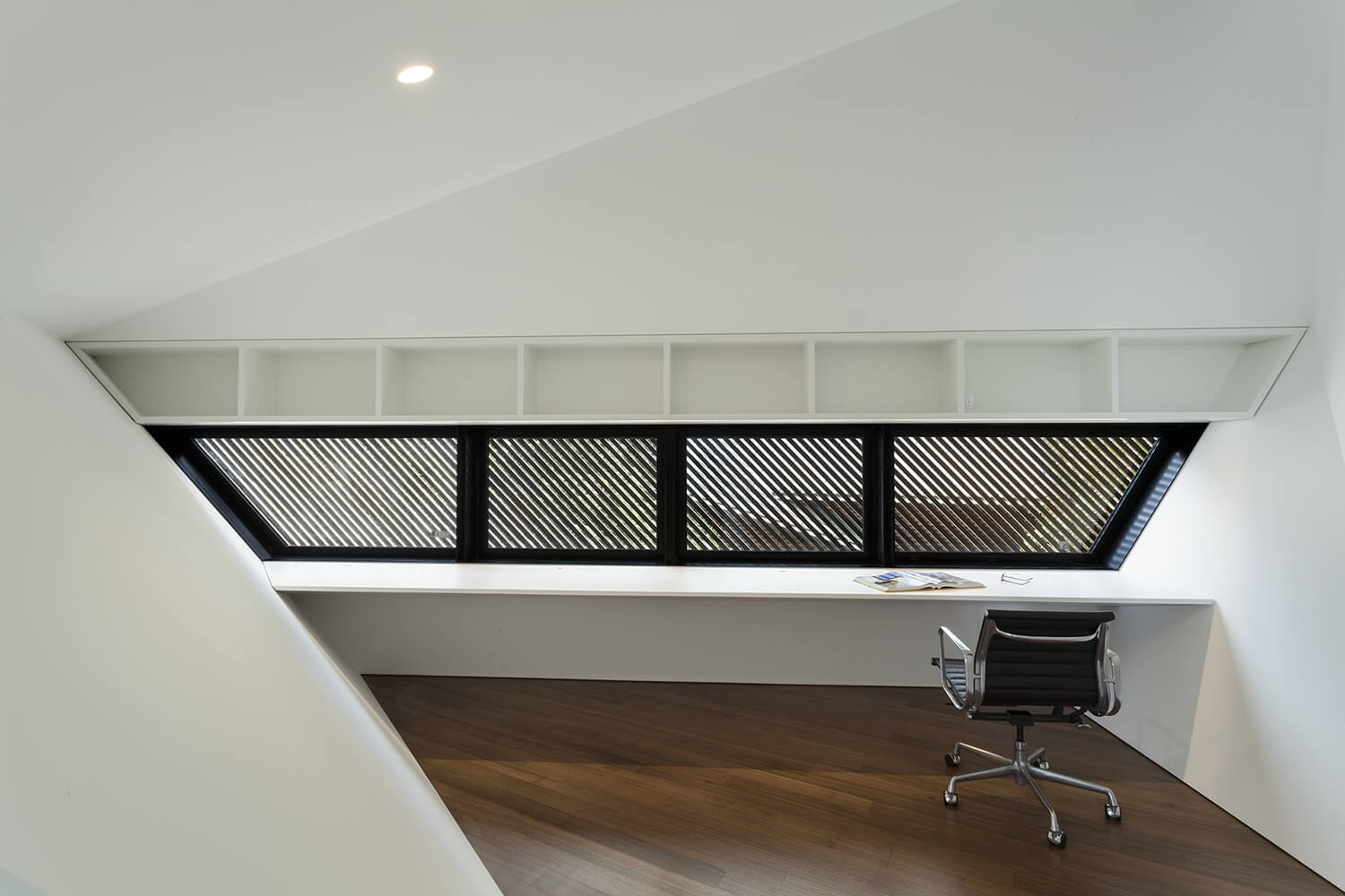 The study is a marvel of minimalist design in white and black. The desk stretches in one piece across the space with plenty of storage.