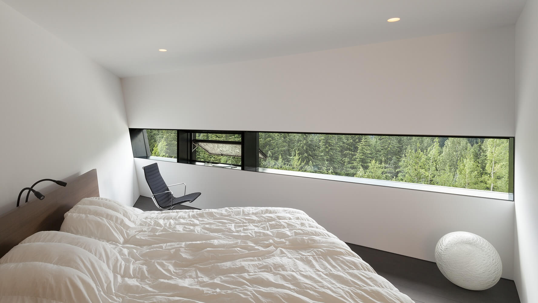 On the other side of the bridge is the primary suite, an angular room in white with a narrow panoramic window with a single opening pane. The bed is minimalist, with a low-profile headboard and two small adjustable lamps peeking over the top, perfect for reading by.