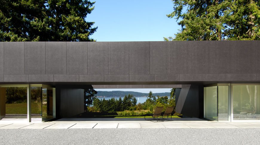 This open-air centerpiece of the structure acts as a roofed patio area, buffered by the home itself on either side. Views over the surrounding foliage to the lake and beyond are available nearly everywhere within the property.