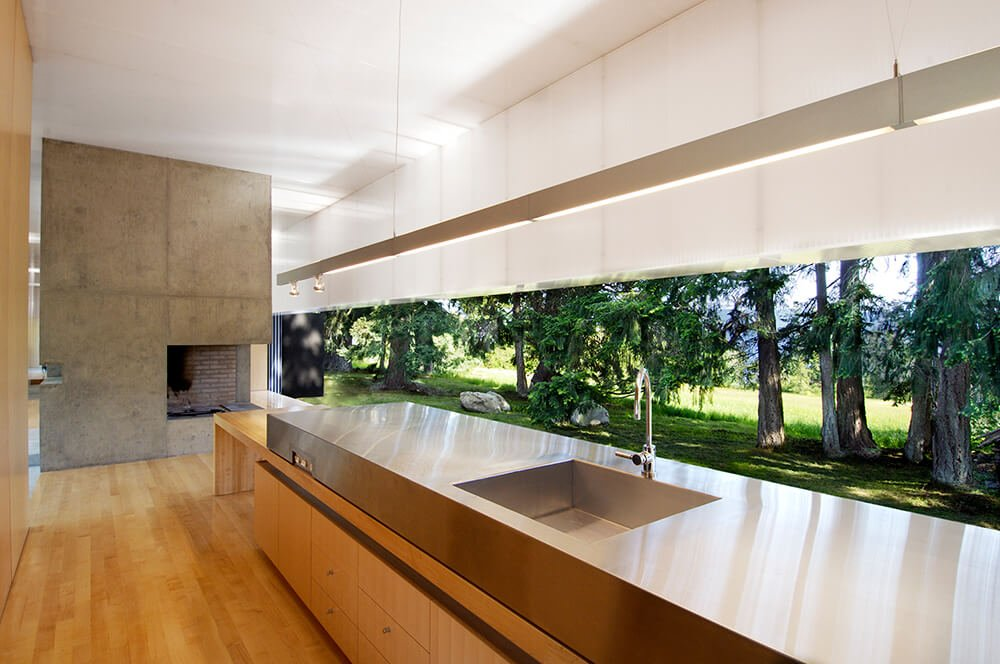 "A raised stainless steel portion of the island houses the ""working"" area of the kitchen, with a large sink at center. From here we see one of the concrete fireplace segments, dividing the home into smaller pieces."