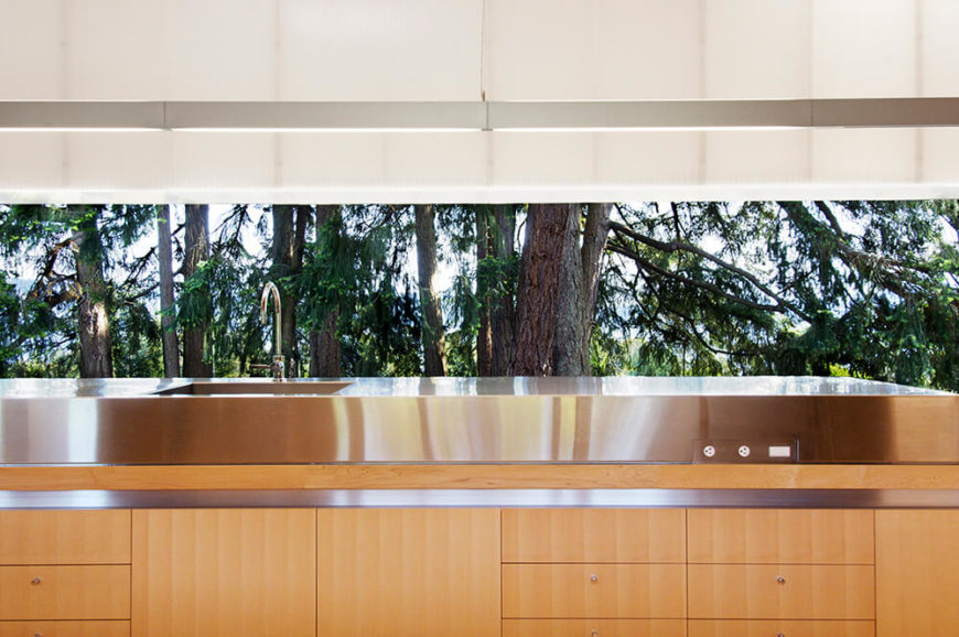 The massive kitchen island flaunts its modern construction, with sleek natural wood cabinetry and stainless steel interplaying. Over the countertop, we see the seamless expanse of nature brought into view by the large opening panels.