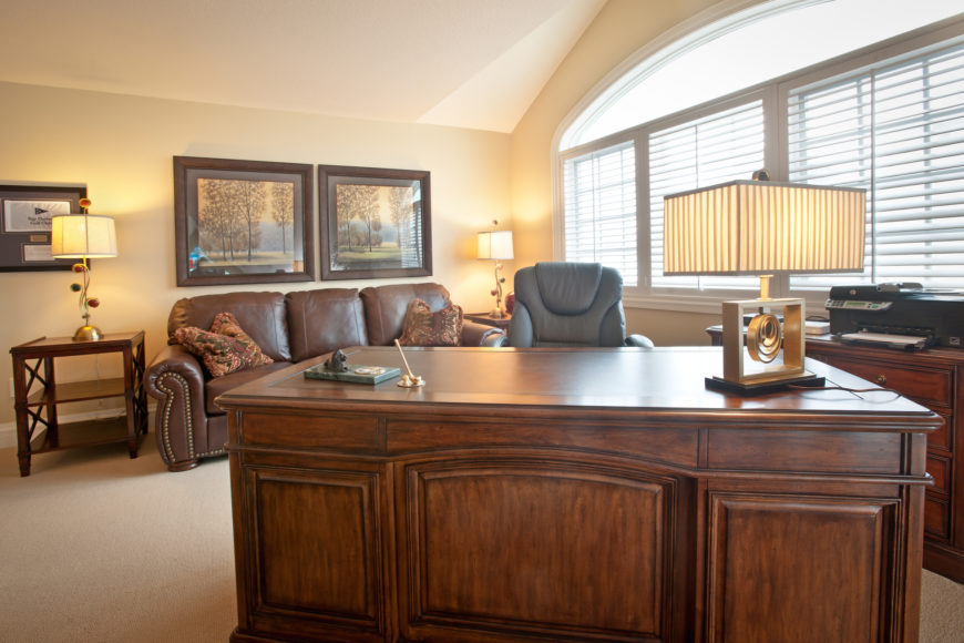 Here we have a large home office, centered on a massive oak desk. Abundant sunlight pours through the large windows over rich wood dresser and table, as well as the nailhead trim leather sofa at the far wall.