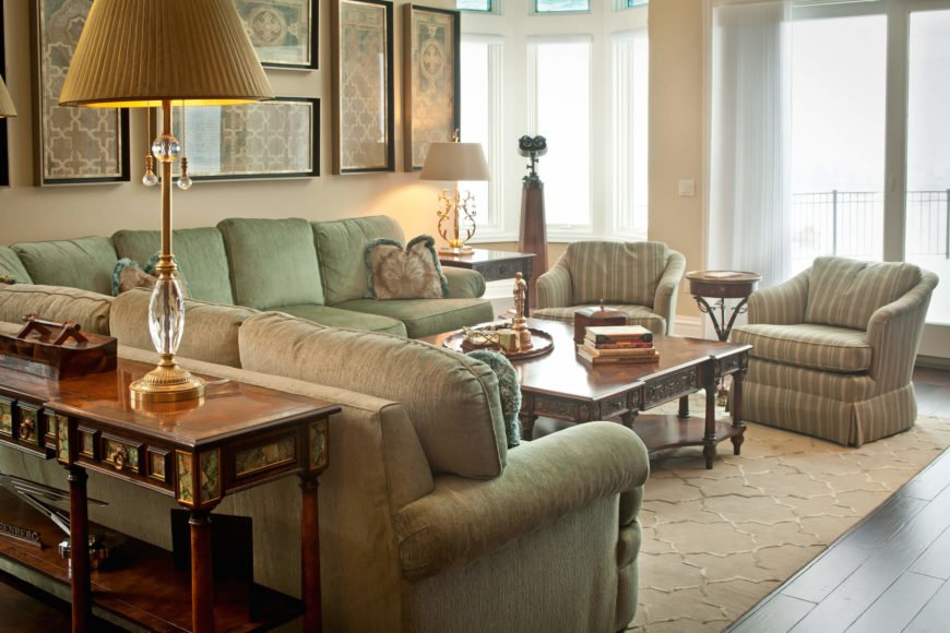 Bracketing the space is a set of full height windows and sliding glass doors on the exterior, and polished side table with glass accents, in foreground. The detailed woodwork on the table is indicative of the type of style seen throughout the home.