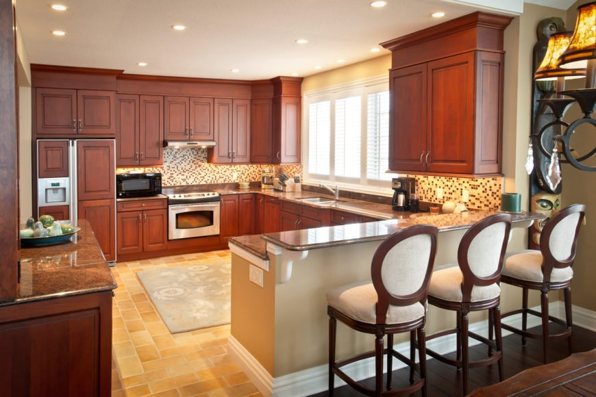The kitchen is wrapped in granite countertops and rich wood cabinetry. A raised countertop allows space for a set of barstools at right, while micro-tile backsplash provides contrast.
