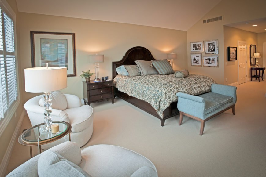 The primary bedroom sports a beige and white palette, spiked by the appearance of light blue in the form of a bench seat and accent pillows on the bed. The rich wood bed frame is flanked by matching bedside dressers, while a pair of white club chairs flank a glass topped table beneath windows at left.