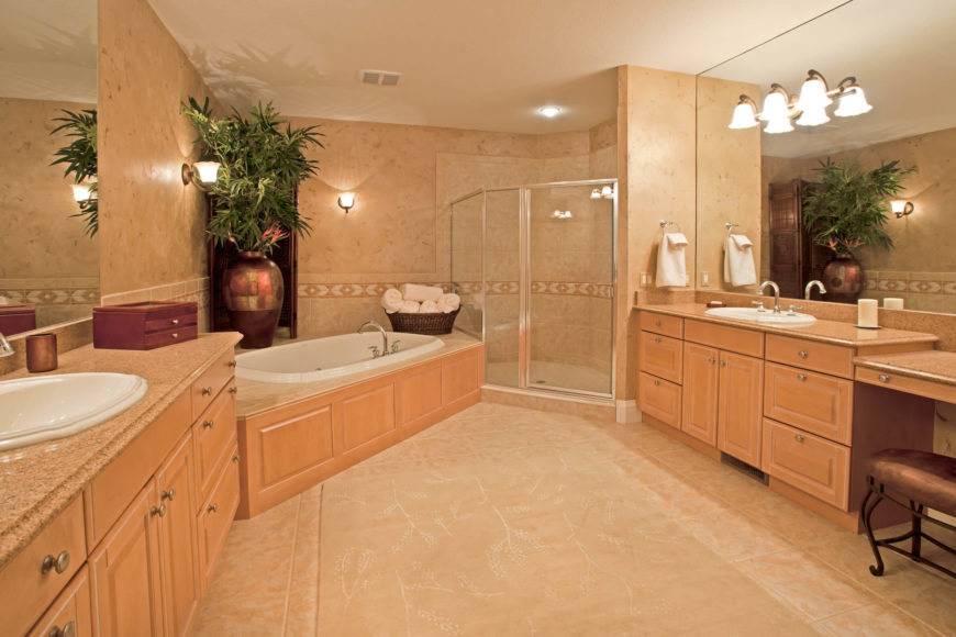 The primary bath is awash in light natural wood cabinetry and beige tile flooring and bath surround. The large space holds enough room for two full vanities with massive mirrors, while the soaking tub fills a corner next to the glass enclosed shower.