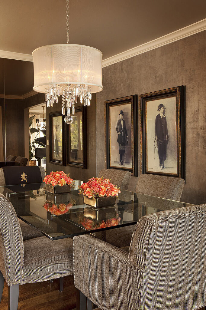 The attached dining room features a darker palette, centering on a glass dining table and set of mocha upholstered chairs, with shade-wrapped chandelier above. A full mirror wall extends the space visually.