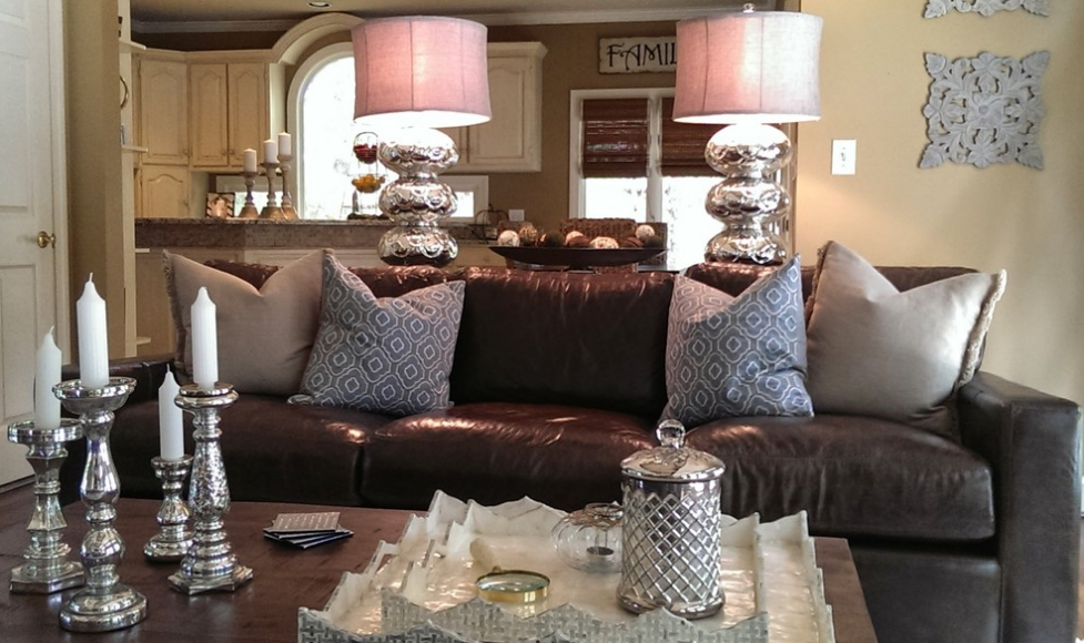 Moving even closer, we get a close look at the textured pillows on the rich leather sofa, as well as details like the carved wall art and trio of candle holders on the kitchen countertop.