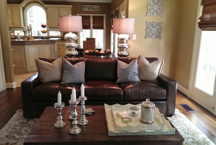 Moving in closer, we catch a glimpse of the rich dark natural wood coffee table, centered on a white shag rug in the living room. Silver candle holders and tabletop treys echo the bright contrast of the lamps.