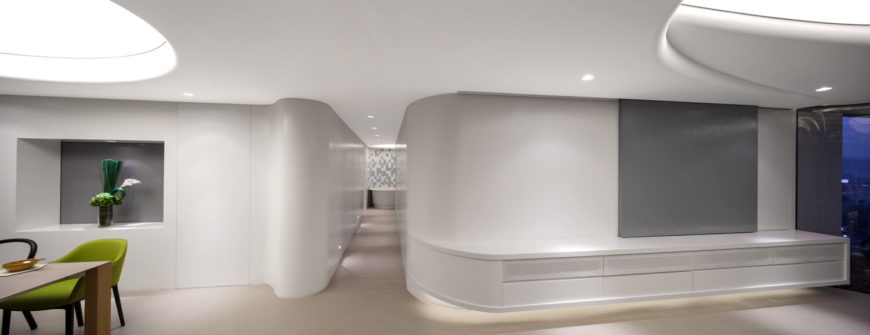 A long and slender hallway moves from the main space to peek into the bathroom. The rounded walls pulling open into the dining room and living room to display the entrance.