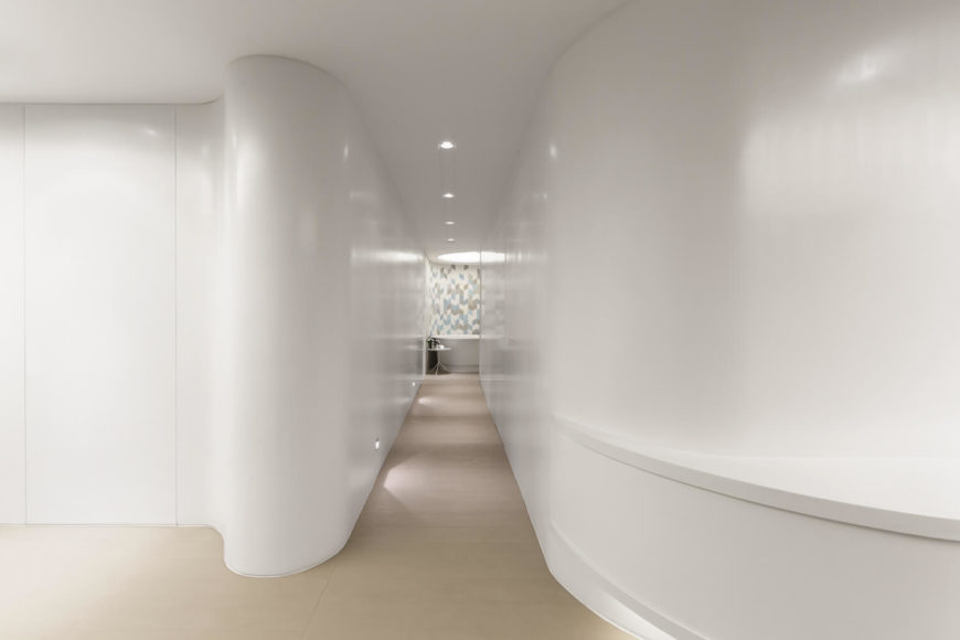 A partial reveal draws occupants down a smooth corridor and into the communal bathroom. Dainty lights both on the ceiling and wall highlight the charming opening to give it a graceful entrance.