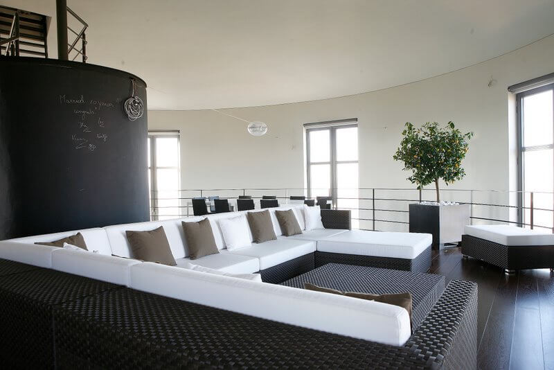 On the opposite side of the chalkboard staircase is a massive black wicker sectional topped with pristine white cushions and accented with dark taupe pillows. An ottoman can be pushed up against the chaise or used as extra seatin