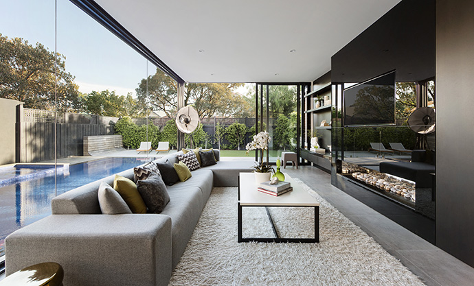 The living room sits beside the pool outside, and a dark glossy entertainment center reflects onto the landscaping. A contemporary color scheme in the furniture matches the color of the flooring and walls of the home.