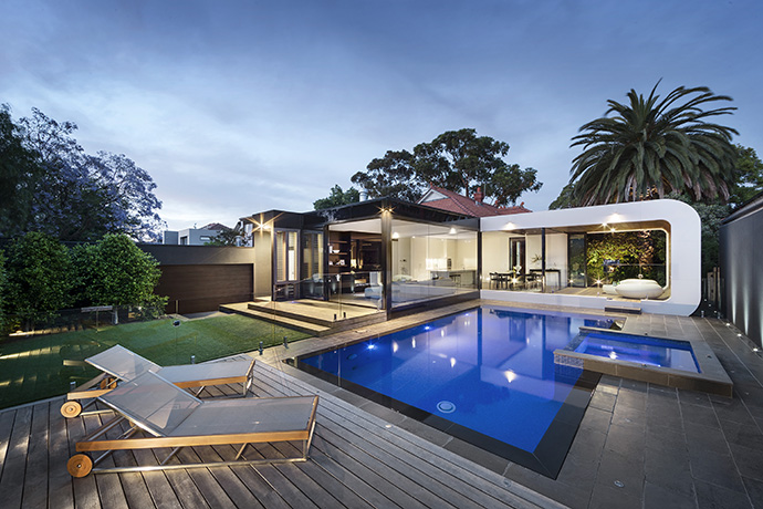 The back of the home consists of unique glazing, exposing the kitchen, living room, dining room, and 3-seasons room. The landscaping mimicks the modern design from the backside of the house, and pulls it into the patio– modernizing the outside with grey concrete and a brilliant blue pool.
