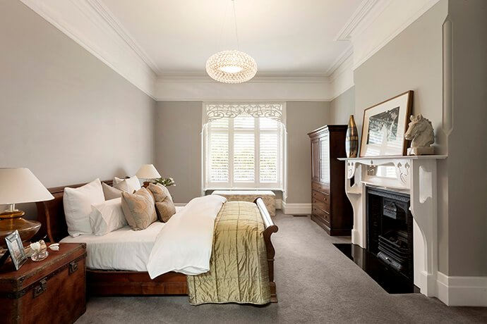 The original part of the home contains elegant furnishing, like this bedroom equipped with a gorgeous vinyl mantle. An intricate design in the window and a delicate light fixture ties the fashionable scheme together.