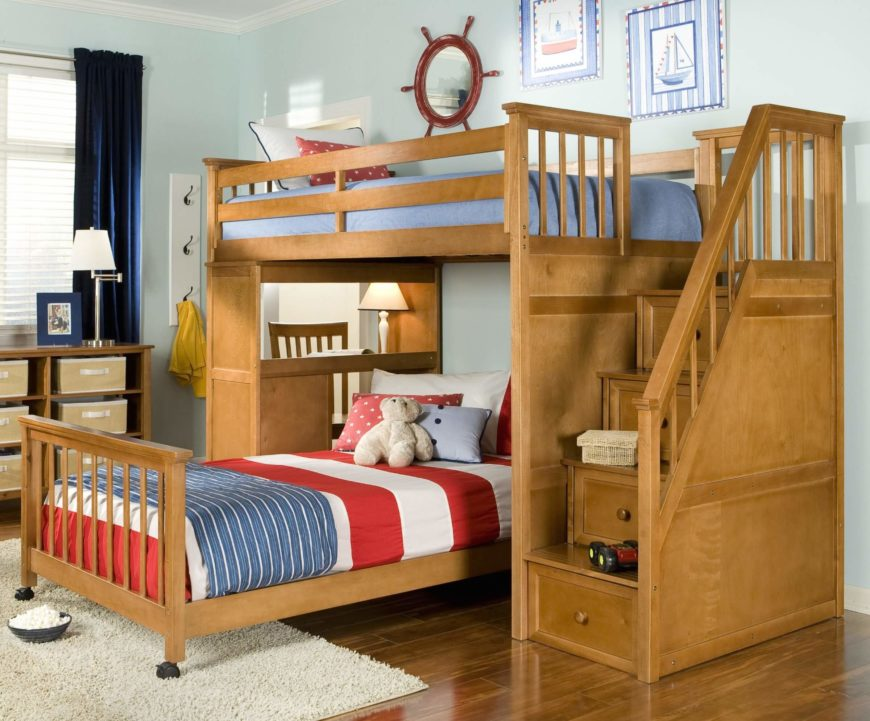 This pecan-tinted natural wood frame bed features a large set of stairs with built-in drawers on the right side, flanked by an elaborate staircase railing. Perpendicularly mounted lower bunk is detachable, while a computer desk is built into the other end.