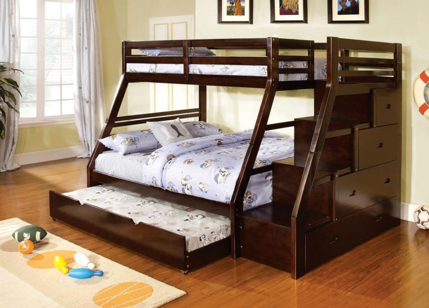 This elegant bed frame in a modern, angled construction features a third bed, a trundle, tucked beneath the lower bunk. Stairs on the right side of the frame conceal side-mounted drawers.