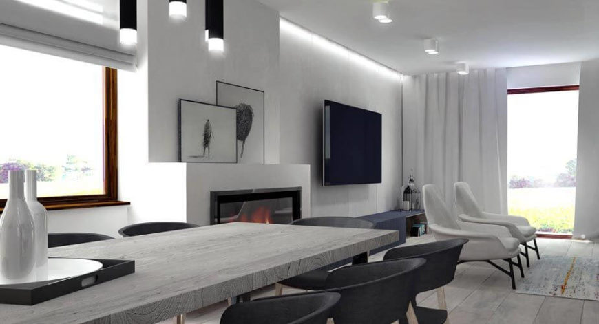 The dining room features a large all-wood dining table in gray and low-profile black dining chairs. The room continues into the living room, with an enclosed gas fireplace between the two spaces.