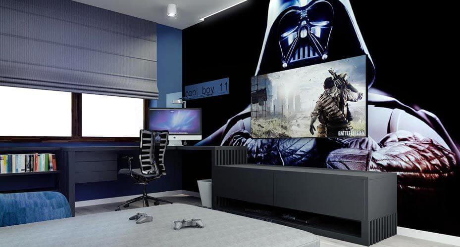 A view of the desk area that continues into a lower entertainment center that contains multiple game consoles. The wall behind the television is covered in a Darth Vader mural.