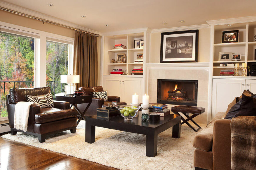 Turning the opposite direction in this large open space, we see a second full set of furniture revolving around a large dark wood coffee table and marble wrapped fireplace. The full height windows let daylight pour into the brightly hued space.