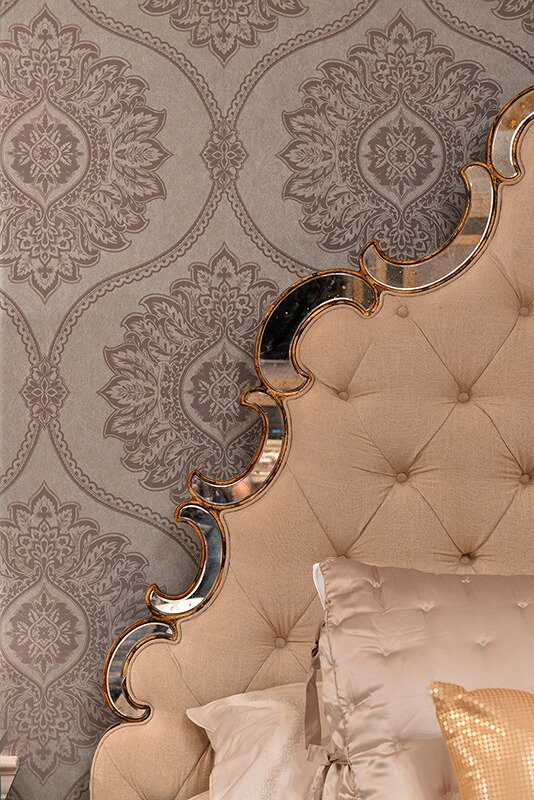 Another incredible detail is the headboard. Far from a simple square headboard, this one is upholstered in button-tufted beige linen and rimmed in crescents of chrome and gold. The curve complements the curved pattern of the wallpaper as well.