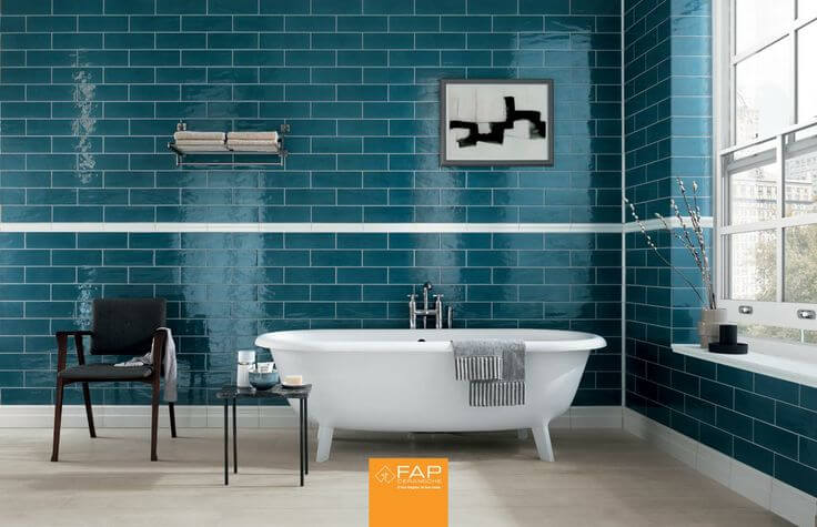 This unique bathroom has an aqua colored tile along the walls. The aqua against the light hardwood flooring the glistening white bathtub adds a striking atmosphere in this space.