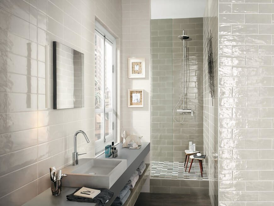 This quaint bathroom has small wooden stools in the shower for extra storage space. The vessel sink is a unique square shape for geometrical touch to this room.