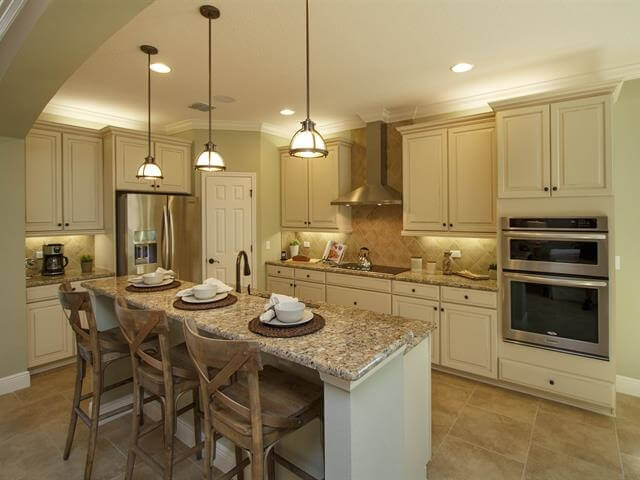 This elegant kitchen has a soft color scheme. The sandy colors in the cabinets and the dim low hanging lights create a comfortable and warm space.