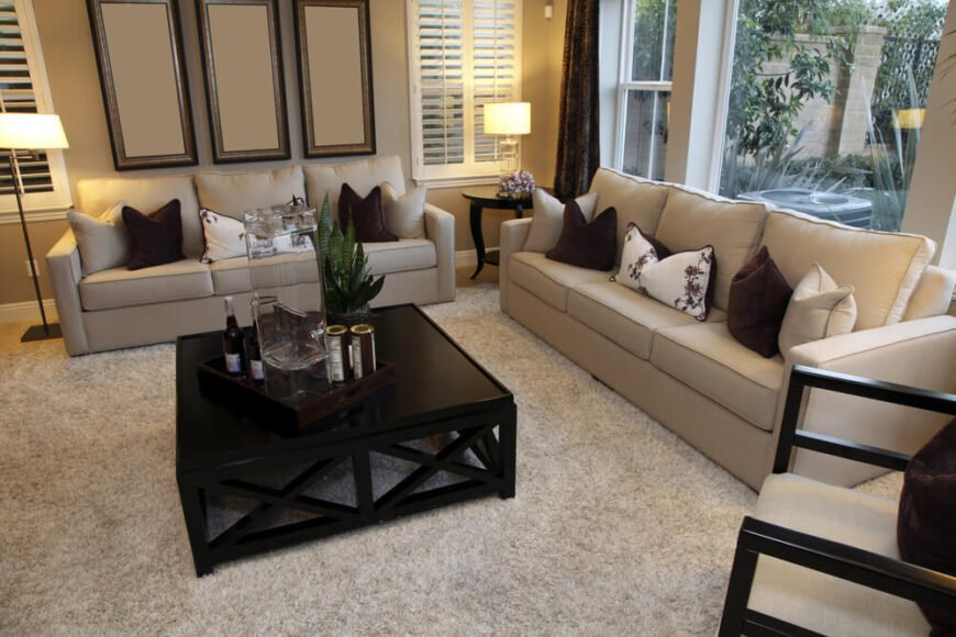 Beiges, creams, and deep chocolate brown work together to create a small living area that is comfortable and pleasing to the eye. Pops of white in accent pillows and shutters provide added interest, while a large picture window peeks into a garden.