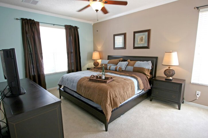 Blues, browns, and charcoal bedroom furniture highlight a small bedroom that is both stylish and attainable. The dark gray bed, end tables, and television stand work perfectly with the light blues and browns of this simple yet elegant space.
