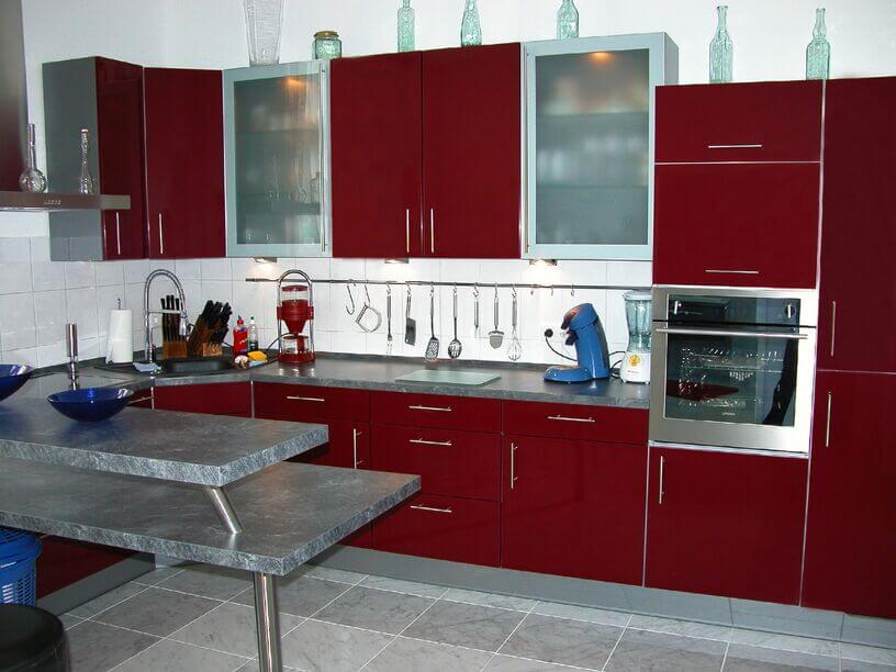 This grey and white kitchen is accented with fierce dark red cabinetry. The rich hue contrasts well with the light colors on the floor and backsplash.
