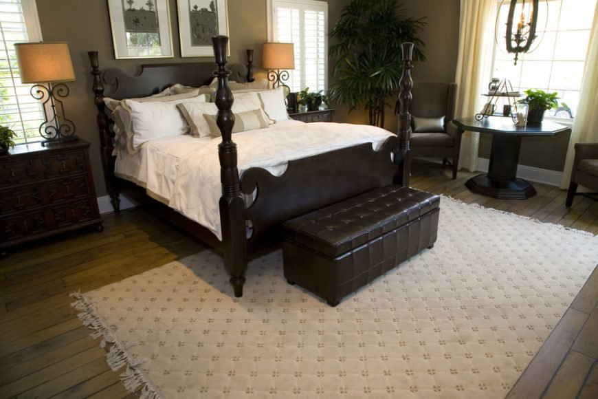 This impressive primary bedroom features an extremely deep brown four post bed, leather chest bench, and coordinating end tables. The ornate metal lamps with light shades offer a soft ambiance, while a natural hardwood floor is dressed up with a large, light area rug. This thoughtfully designed space ensures that window space allows sunlight to flood through the room from multiple angles.