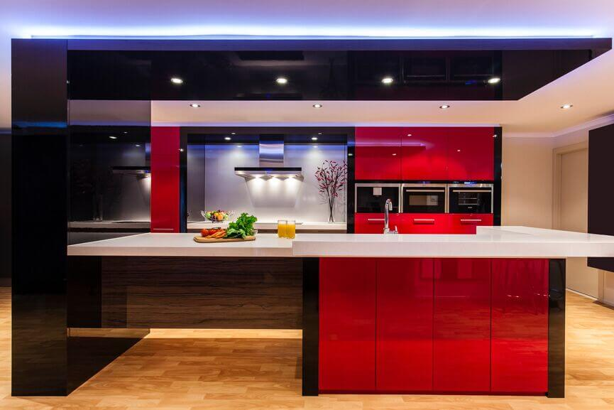 The main source of light here filters down from colored lights that line the ceiling. The cool tones in the lights bring out the vibrant red and black in the glossy cabinets and countertops.