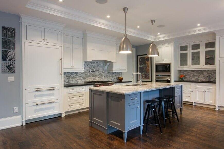 This kitchen features crisp white cabinetry. The flooring is a smooth hardwood kissed by the delicate lighting of brushed stainless steel fixtures.