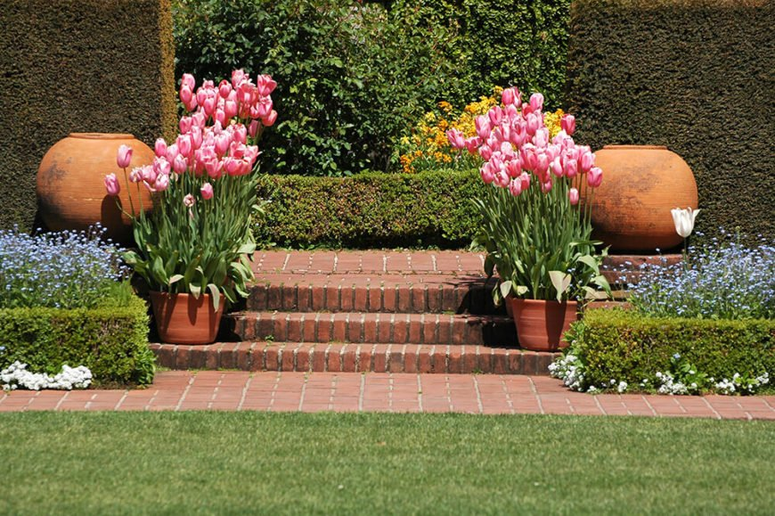 The use of these low hedges to surround the flower beds while backing them with the tall, imposing hedges adds a sense of balance to this garden.
