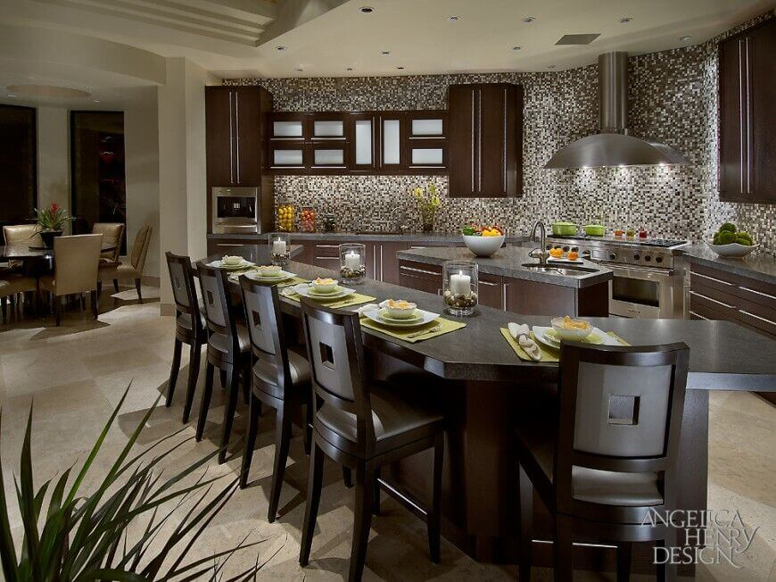This kitchen is dappled with a small tile backsplash, complemented by grey stone countertops.. The bar is made of a rich deep chocolate hardwood, and laced in white light.