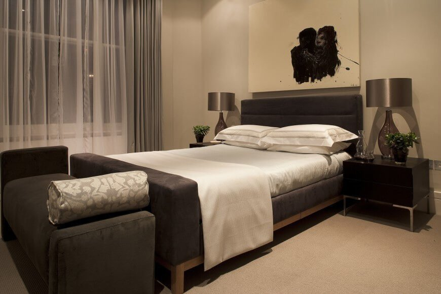 This small bedroom area features a beautiful, soft, chocolate brown bed and bench. The cream carpeting, drapery veil, and lighter linens work together to create a space both cohesive and high in contrast. Simple black end tables hold high sheen glass lamps, while a large and stunning piece of modern art ties the room together.