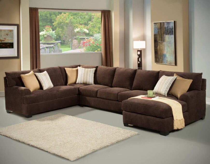 A large chocolate sectional sits atop a matte gray floor. An ivory area rug breaks up the space, while throw pillows coordinate with the buttery gold of the walls. A large picture window looks into a gorgeous garden, while a modern painting offers bursts of complementary blues.
