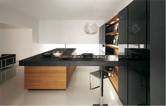 This U-shaped kitchen connects the storage spaces, bar, and island of light hardwood and black countertops. Lights are tucked under the wall in the far end of the kitchen to softly illuminate the room.