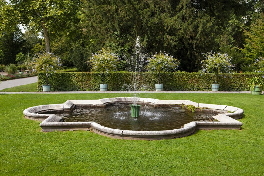 The clean, flat lines of this hedge balance out the beautifully arching water and curves of the fountain base. The small potted flowering trees add additional points of interest.