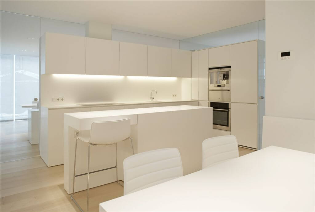 This minimalistic kitchen has gorgeous glossy white countertops and cabinets. Under cabinet lighting brings out a soft natural glow.